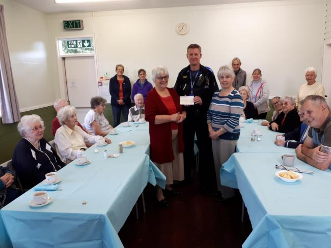 PCSO Mike Handford presenting a cheque for £250 to The Redditch Association for the Blind