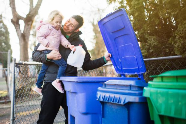 A dad holds his daughter as he teaches her about the environmentally friendly practice of recycling plastic and cardboard waste. Library picture. Getty Images