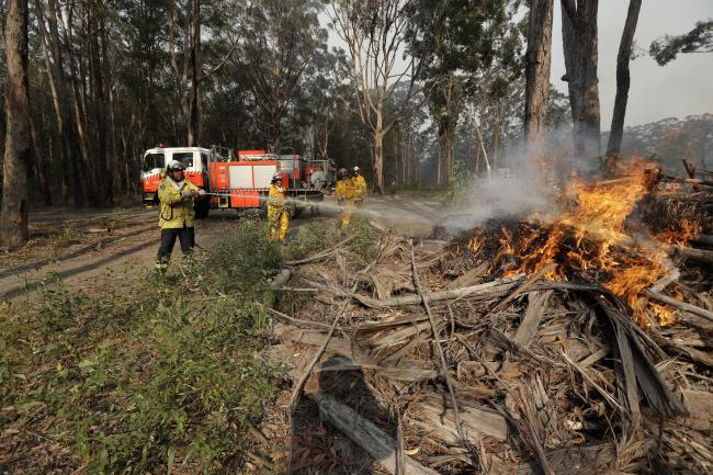 Firefighters battle a fire near Bendalong, Australia. Picture: AP Photo/Rick Rycroft