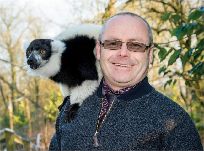 of Zoo Director Derek Grove with a black-and-white ruffed lemur