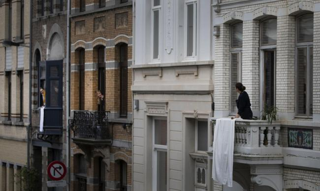 ISOLATION: We could be getting used to scenes like this. Three women speak with each other from their balconies in Antwerp