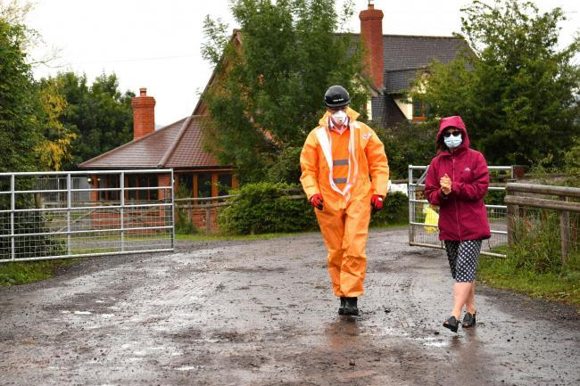 Karen Wright (right), Director of Public Health for Herefordshire CCG, sanitising before opening a gate to give a press statement outside Rook Row Farm in Mathon. Picture: Ben Birchall/PA Wire