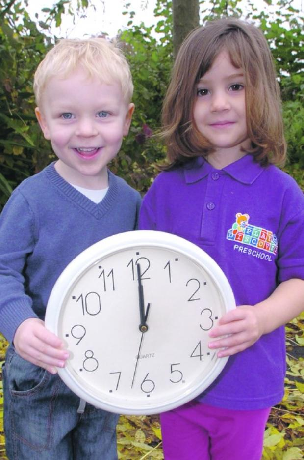 Clocks go back: Play N Discover Pre-School youngsters Daniel Povey and Jasmine Laugher, both aged three, remind residents to turn back their clocks this Sunday. Buy this photo BMM41204a