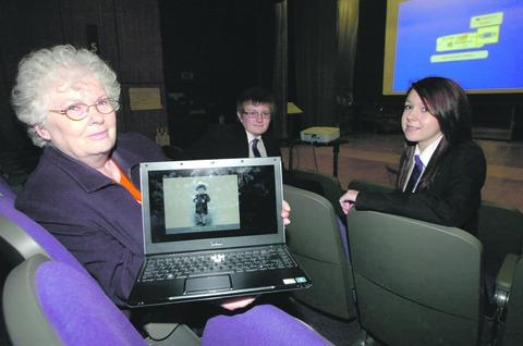 Holocaust survivor Joanna Millan, with a picture of herself as a child, with pupils Callum Wright and Emily King, both 14. Buy this photo RMM501202a