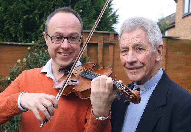 Redditch Advertiser: VIOLINIST: Former vicar Donald Wrapson and the City of Birmingham Symphony Orchestra violinist Byron Parish, with the violin that has raised hundreds for charity. SP