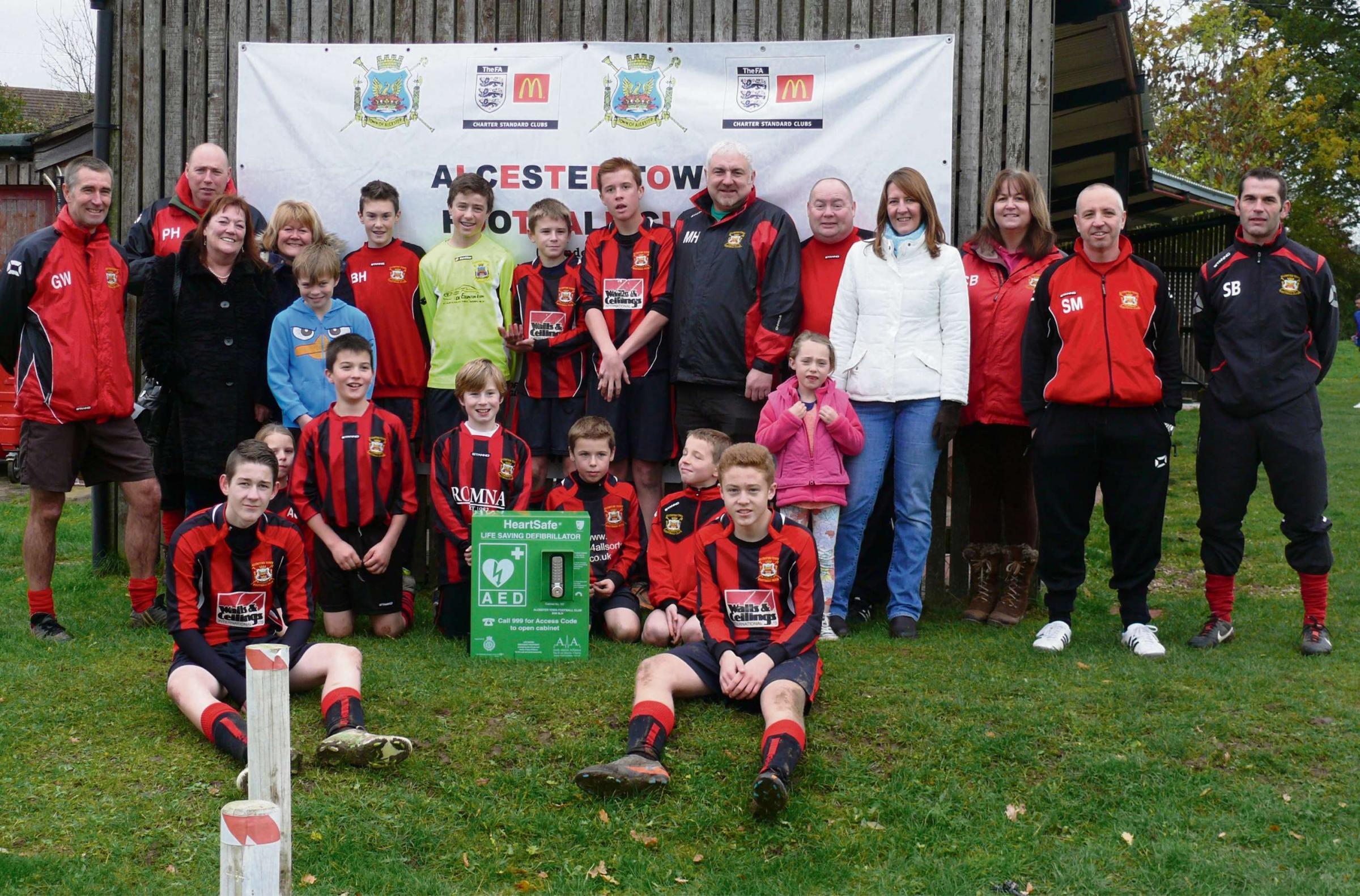 Alcester Heartsafe campaigners Alison Brown and Ann Delany (third and fourth from left) with Alcester Town Football Club and its new defibrill