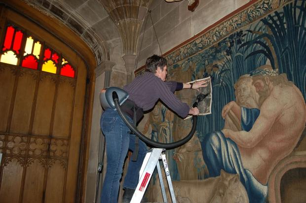 Helen Robertson, the conservation and engagement manager at Coughton Court cleaning the tapestries. Image courtesy of Abi Cole. SP