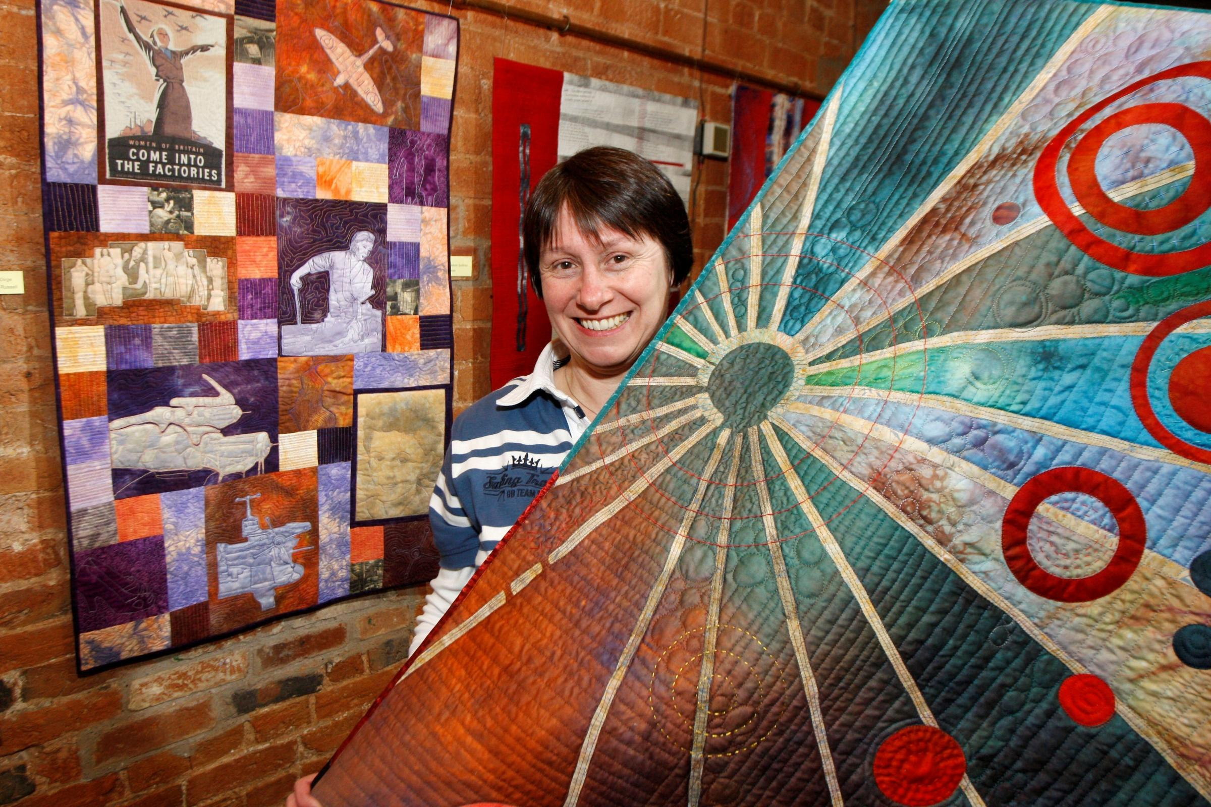 Jo-Anne Gloger seen with a colourful Qwilt at Forge mill exhibition