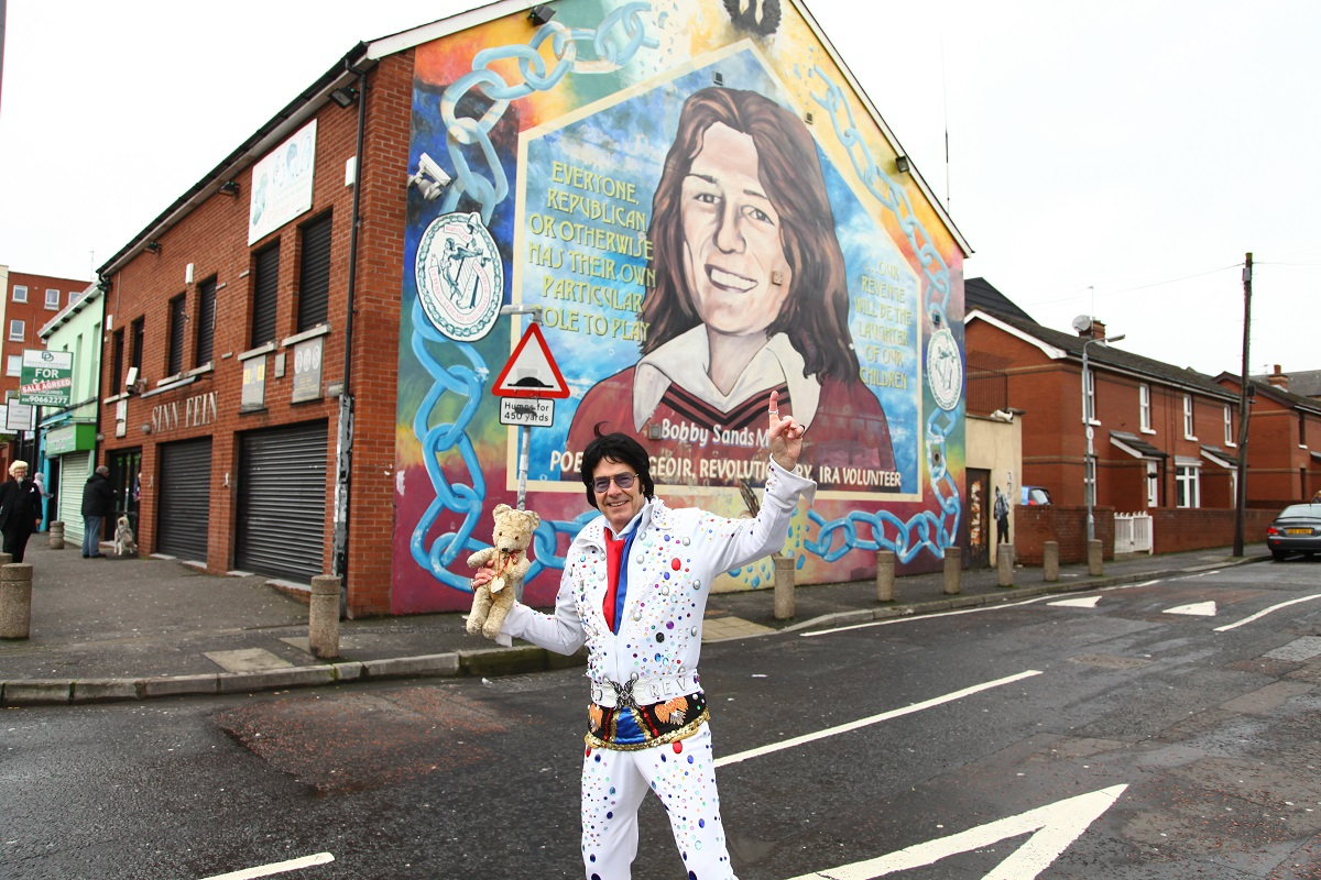 Andy Kelso on the Falls Road in Belfast, near a mural of Bobby Sand, a Provisional IRA member who died on hunger strike while imprisoned at HM Prison Maze in 1981.