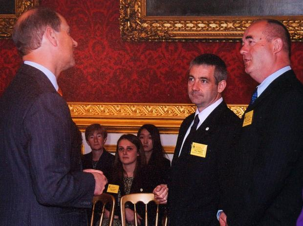 Redditch Advertiser: RECOGNITION: Ron Jackson, right, and Guy Rogers, centre, receiving their awards from Prince Edward.