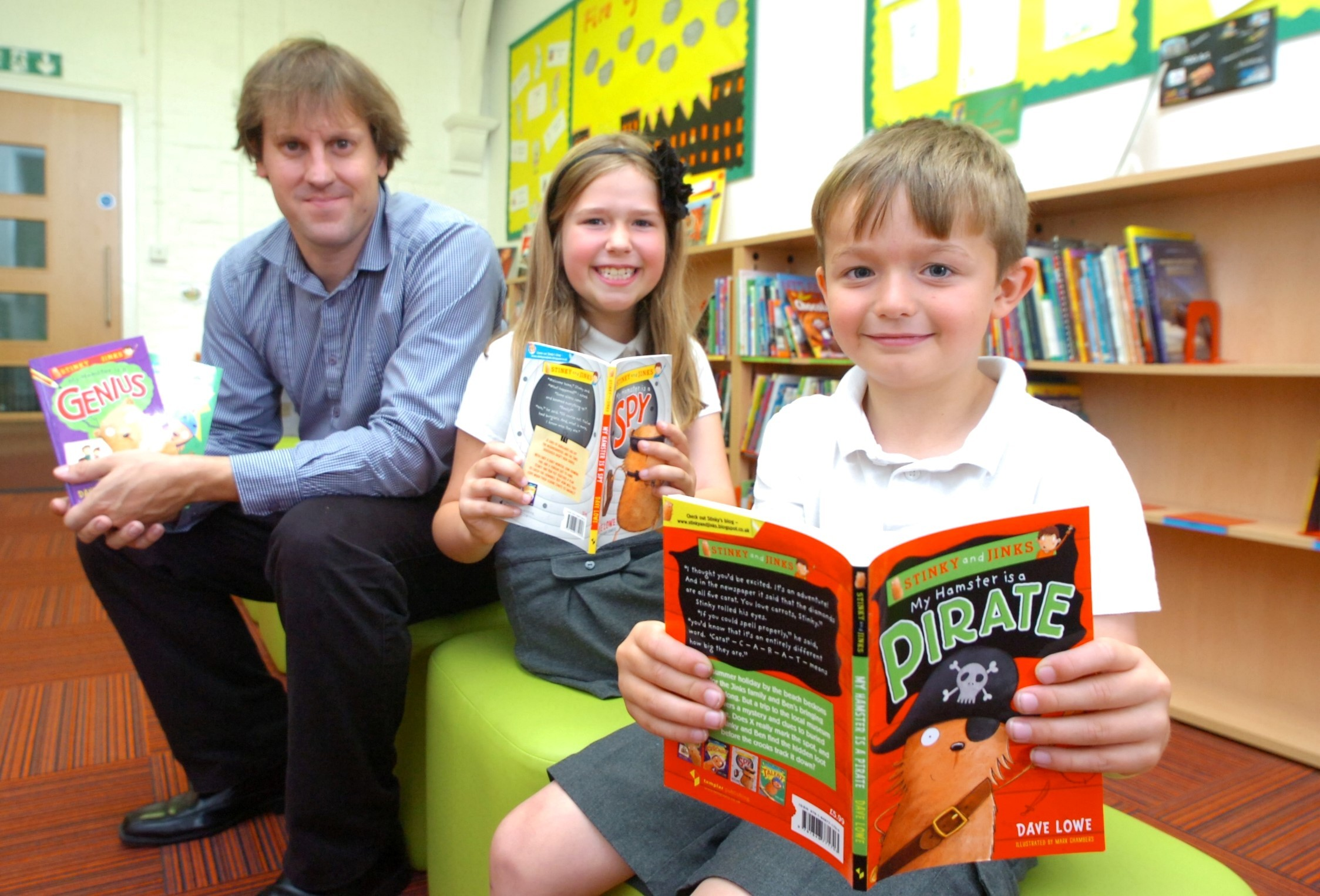 Pupils Bailey Holder and Katie Livett, both aged seven, with author Dave Lowe. Buy this photo RMM281402 at redditchadvertiser.co.uk/pictures
