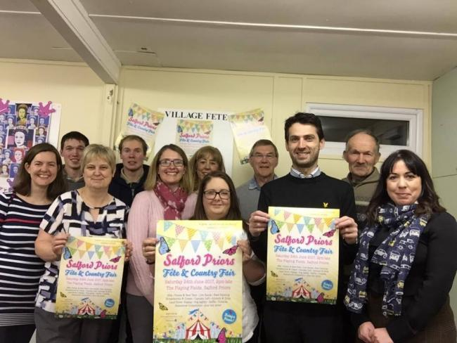 Salford Priors fete commitee pose with event posters.