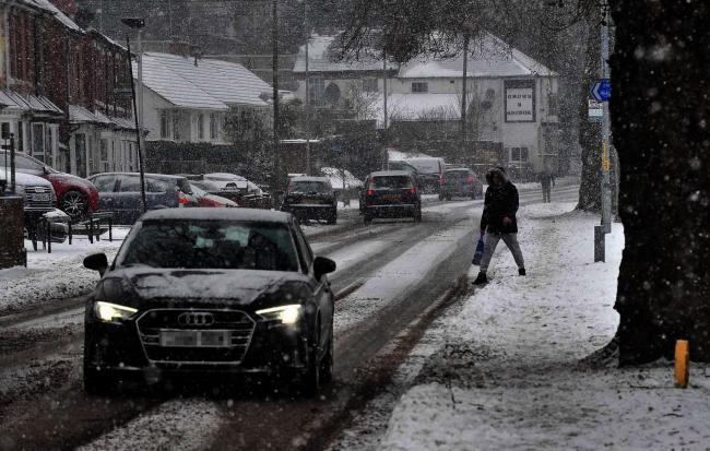 Motorists and pedestrians battle with snow. Photo: Jonathan Barry