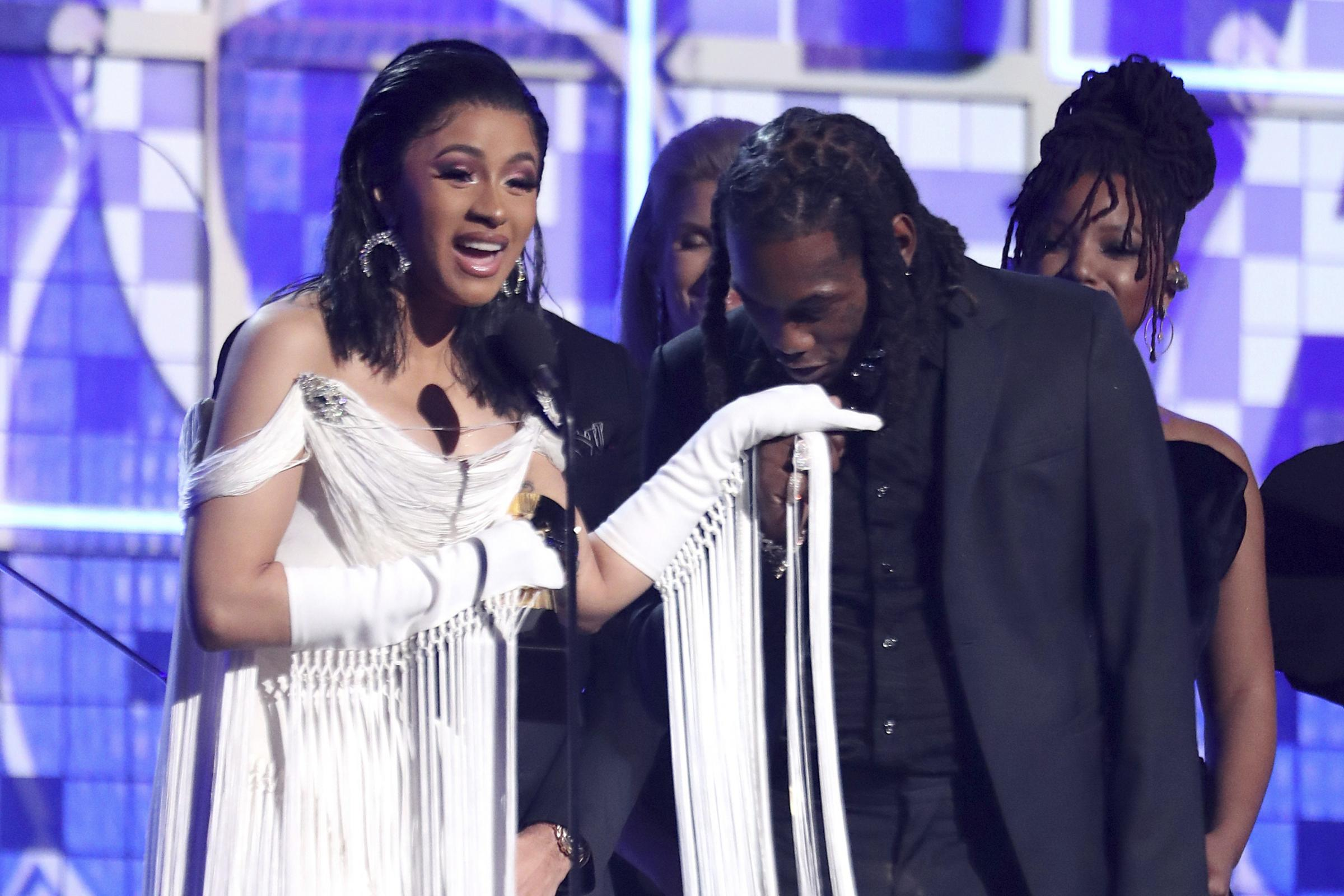 Cardi B accepts the award for best rap album as Offset kisses her hand