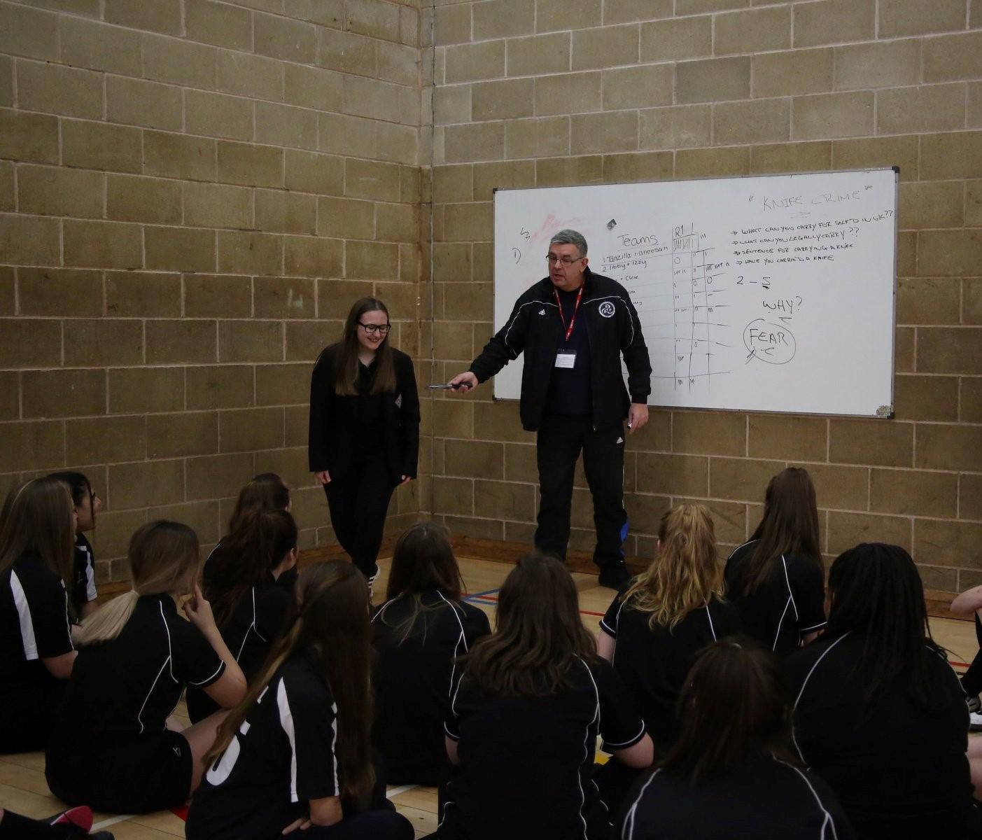 Pete Martin, with rubber knife, talking to pupils